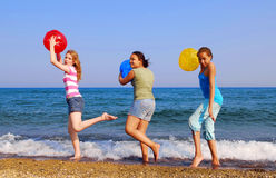 Girls on beach. Three girls with colorful beach balls walking on sea shore Royalty Free Stock Photo
