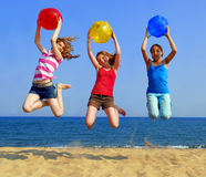Girls on beach. Three girls with colorful beach balls jumping on a seashore Stock Photography