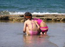 Girls on the beach. Girls exploring marine life, on the beach, in Greece Royalty Free Stock Photo
