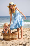Girls on the beach with a basket Royalty Free Stock Images