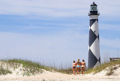 Girls by beach lighthouse Royalty Free Stock Photography