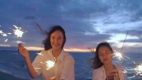 Girls on the beach with sparklers. Two girls on the beach celebrate, dressed in white shirts with sparklers on the background of the sea and the sunset stock video