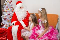Girls in beautiful dresses talk with Santa Claus Stock Photo