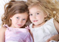 Girls in bed having a sleep-over looking up Stock Image