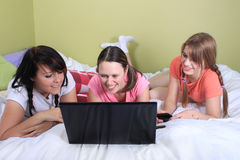 Girls on bed using laptop. Group of three teenage girls with pigtails and braided hair having a slumber party or sleepover laying on a bed using a laptop and Stock Images