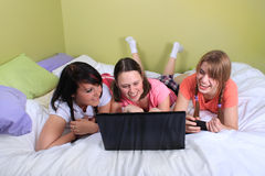 Girls on bed using laptop. Group of three teenage girls with pigtails and braided hair having a slumber party or sleepover laying on a bed using a laptop and Stock Photo