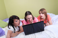 Girls on bed using laptop. Group of three teenage girls with pigtails and braided hair having a slumber party or sleepover laying on a bed reacting to screen on Stock Photography