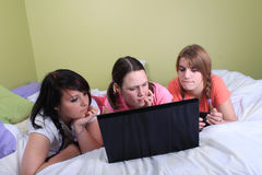 Girls on bed using laptop Stock Photo