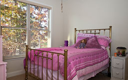 Girls Bedroom. An antique brass bed beside the windows in a girl's bedroom Royalty Free Stock Image