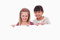 Girls behind a blank panel Stock Images