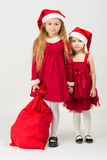 Girls in the bell Santa Claus with a bag of gifts. Two girls in a red dress in the bell Santa Claus with a bag of gifts Royalty Free Stock Images