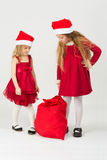 Girls in the bell Santa Claus looking on a bag Stock Image