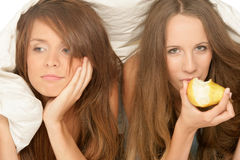 Girls below duvet. Two teenage girls below duvet stock photo