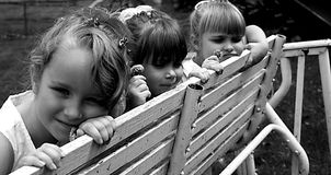 Girls on the bench. Three girls sitting on a bench holding flowers royalty free stock photography