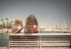 Girls on the bench watching the harbor Stock Image