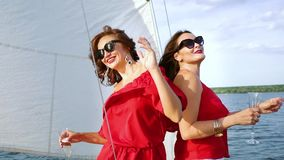 Girls best friends having party with alcohol on sailboat. Two happy women in red clothes and sun glasses dancing with wine glasses on sailboat. Best friends stock footage