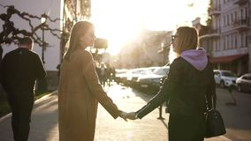Girls best friends holding hands while standing on the street. View of two stylish girls spending time together on the. Pavement in the city. Friendship and stock video footage