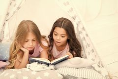 Girls best friends read fairy tale before sleep. Best books for kids. Children read book in bed. Reading before bed can. Help sleep better at night. Stories royalty free stock photo