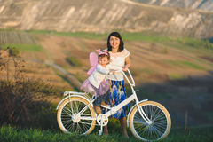 Girls with Bicycle at Sunset Royalty Free Stock Images