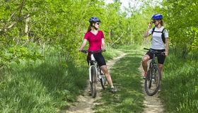 Girls  biking on a  forest road Stock Photo