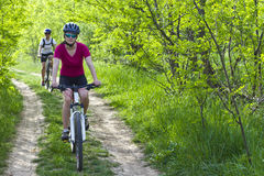 Girls  biking in the forest Stock Image