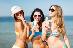 Girls in bikini with ice cream on the beach royalty free stock images