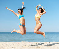 Girls in bikini jumping on the beach Stock Photo