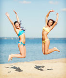 Girls in bikini jumping on the beach Royalty Free Stock Photos