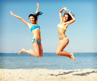 Girls in bikini jumping on the beach Stock Photos