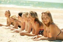 Girls in bikini lying on beach. Photo of several girls in bikini lying on sandy beach and tanning in the bright summer sun Stock Image