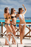 Girls in bikini relax on the background of the ocean. Three young girls with beautiful figure, two girls in black - one in a white bikini, sunglasses, wearing a stock photography