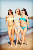 Girls in bikini walking on the beach Stock Photography