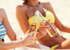 Girls in bikinis with drinks on the beach chairs Royalty Free Stock Photos