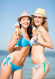 Girls in bikinis with ice cream on the beach Royalty Free Stock Image