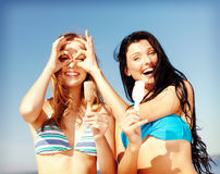 Girls in bikinis with ice cream on the beach Stock Image