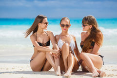 Girls in bikinis sunbathing, sitting on the beach. Three young girls with a nice figure, two girls in black, one in white bikini, sun glasses,arm bracelet stock image