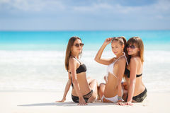 Girls in bikinis sunbathing, sitting on the beach. Three young girls with a nice figure, two girls in black, one in white bikini, sun glasses,arm bracelet stock photo