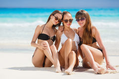 Girls in bikinis sunbathing, sitting on the beach. Three young girls with a nice figure, two girls in black, one in white bikini, sun glasses,arm bracelet stock photos