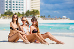 Girls in bikinis sunbathing, sitting on the beach. Three young girls with a nice figure, two girls in black, one in white bikini, sun glasses,arm bracelet royalty free stock images