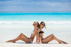 Girls in bikinis sunbathing, sitting on the beach. Two beautiful girls with a good figure, in black and white bikini, sunglasses, wearing a bracelet on her arm stock photography