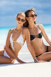 Girls in bikinis sunbathing, sitting on the beach. Two beautiful girls with a good figure, in black and white bikini, sunglasses, wearing a bracelet on her arm royalty free stock photos