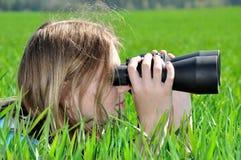 Girls with binocular. Lying Girl looking through binoculars Stock Photo