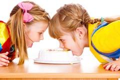 Girls biting cake Royalty Free Stock Photo