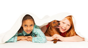 Girls Black and Caucasian under blanket with dog Stock Images