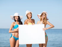 Girls with blank board on the beach. Summer holidays and vacation - girls in bikinis holding blank white board on the beach Stock Photo
