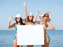 Girls with blank board on the beach Stock Photo
