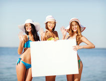 Girls with blank board on the beach Stock Photos