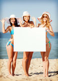Girls with blank board on the beach Stock Photography