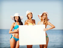Girls with blank board on the beach Royalty Free Stock Photos
