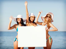 Girls with blank board on the beach Stock Images